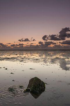 Een eenzame basaltblok op het Wad bij zonsondergang van