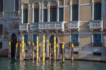 Alte Gebäude mit gelben Pfählen am Kanal in der Altstadt von Venedig, Italien von Joost Adriaanse