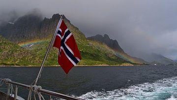 Noorse vlag op de achtersteven van een boot met regenboog en bergen van Timon Schneider