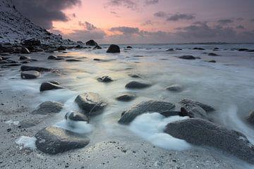 Schnee zwischen den Steinen an einem Strand von Hannon Queiroz