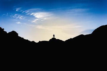 Silhouetten van twee mensen die op de top van een berg staan bij zonsondergang. Wout Kok One2expose van