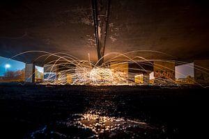 Lightpainting met vuurvonken onder viaduct
