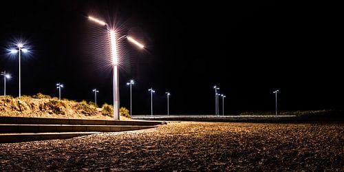 Lantaarnpalen verlichten de parkeerplaats naast het strand van Scheveningen