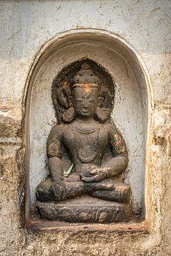 Boeddha beeld in een nis van een witte muur van een tempel in Nepal van Rietje Bulthuis
