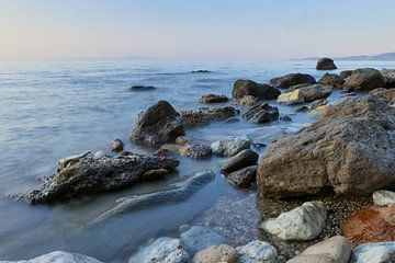 gekleurde rotsten in de zee bij zonsondergang van Eline Oostingh