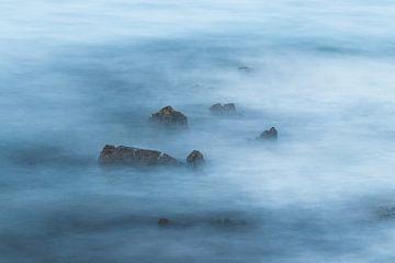 Nevelige blauwe lange blootstelling van rotsen in zee van Patrik Lovrin