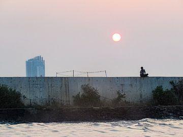 Jongen op muur bij zonsondergang in de oude haven in Jakarta, Indonesië van Daan Duvillier