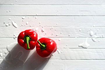 Twee rode paprika's op een witte houten tafel, met waterdruppels van Maarten Pietersma