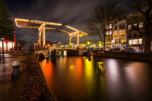 Nieuwe Herengracht met kleurrijke reflecties van verlichting en achter de brug de Amstel