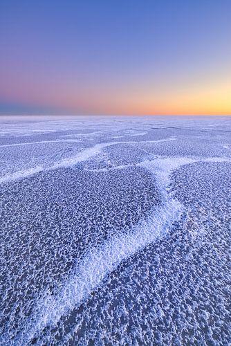 Mooie structuren op een met ijs bedekt IJsselmeer tijdens de winter. Aan de horizon komt de zon lang
