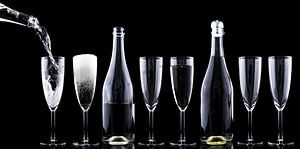 Flaschen und Gläser mit Champagner in dunkler Umgebung