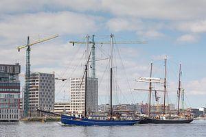 Klassieke twee- en driemaster varen langs de woningen in aanbouw bij de Houthavens in Amsterdam bij