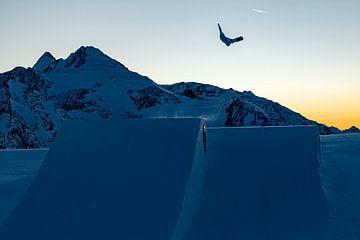 Snowboarder vliegt hoog boven de alpentoppen
