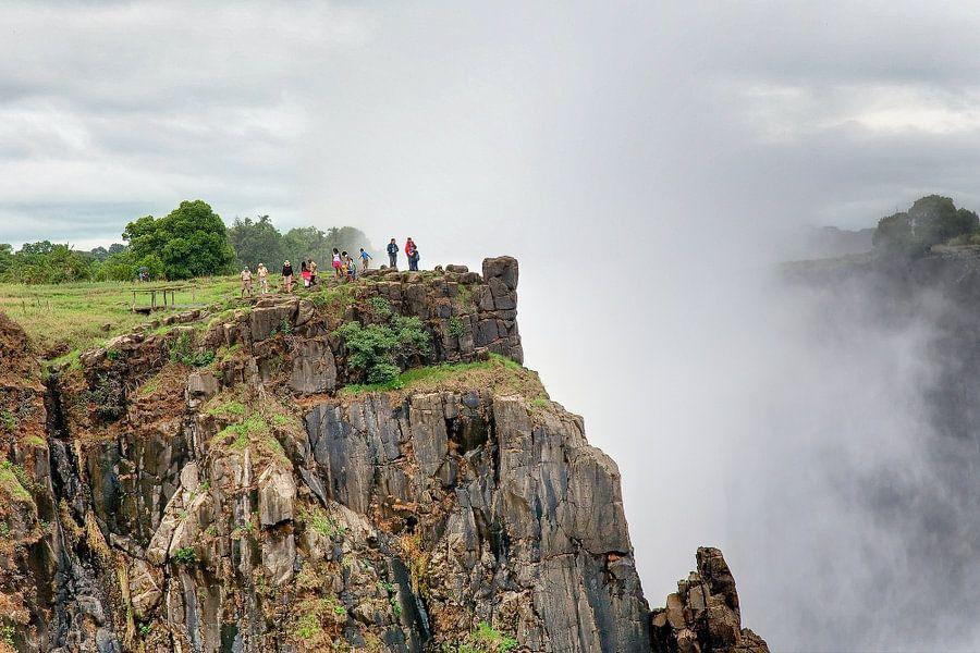 Toeristen aan de rand van de Victoria watervallen
