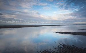 Reflecties op een nat strand bij zonsondergang
