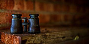 Antieke verrekijker op een stoffige plank van
