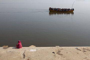 Indiase vrouw kijkt aan de oever van de Ganges in Varanasi naar een passerende boot met hindustaanse van