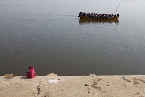 Indiase vrouw kijkt aan de oever van de Ganges in Varanasi naar een passerende boot met hindustaanse
