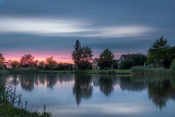 Coucher de soleil à Emmen avec reflet dans le grand lac de roseau sur Kim Bellen