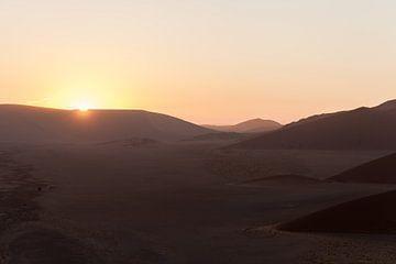Opkomende zon achter duinen in Namibië van Simone Janssen