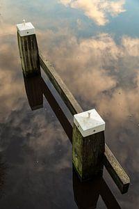 Meerpaal in een weerspiegeling van de wolken lucht in het water. One2expose Wout Kok Photography.