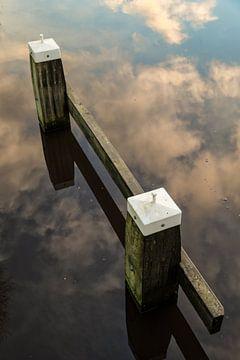 Meerpaal in een weerspiegeling van de wolken lucht in het water. One2expose Wout Kok Photography.  van Wout Kok