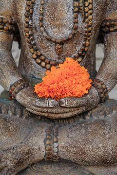 Schöner Buddha mit orangefarbener Blume irgendwo in Ubud. von Jeroen Langeveld, MrLangeveldPhoto