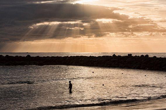 Jongen in de kalme zee bij avondschemering