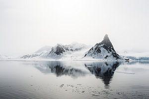 Spitse bergen doemen op uit de nevel