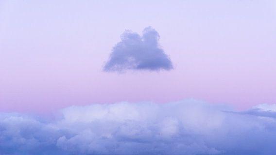 Een kleine donkere wolk zweeft boven een lichte tijdens een zonsondergang