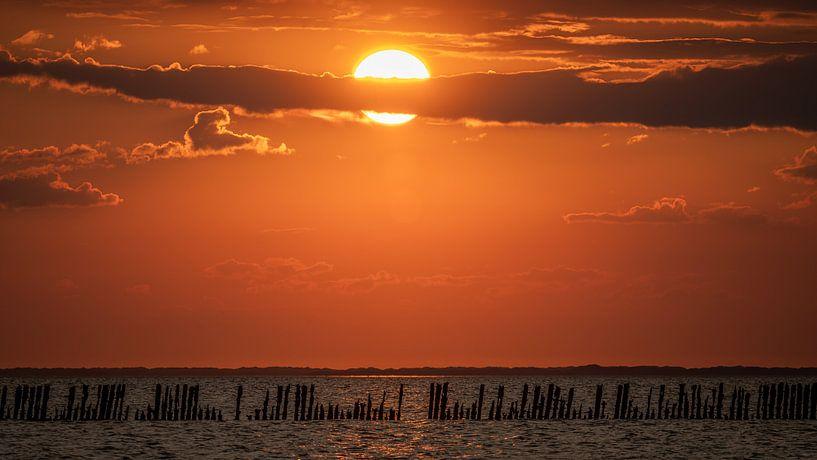 Zonsondergang Waddenzee met een mooie rij palen op de voorgrond. van Martijn van Dellen