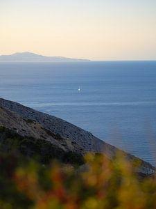 Zeilboot eenzaam in de Egeïsche Zee tussen Santorini en Folegandros, Griekenland van Teun Janssen