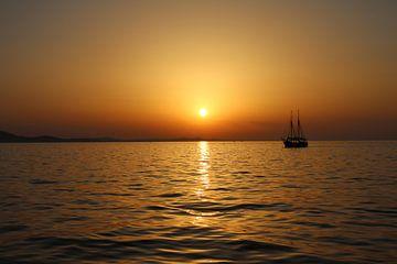 zonsondergang op zee kijkend naar een zeilschip van Evelien van der Horst
