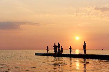 Mensen aan zee tijdens zonsondergang van Harry Wedzinga