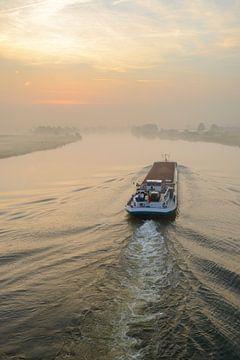 Navire transportant des marchandises en vrac dans un lever de soleil sur la rivière IJssel sur Sjoerd van der Wal