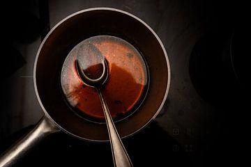 pot en lepel met runderbouillon tijdens het koken van een rode wijnmorelsaus op een zwart fornuis, d van Maren Winter