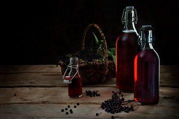 Zelfgemaakt sap van zwarte vlierbessen (Sambucus nigra) in flessen en bessen in een mandje op rustie van Maren Winter