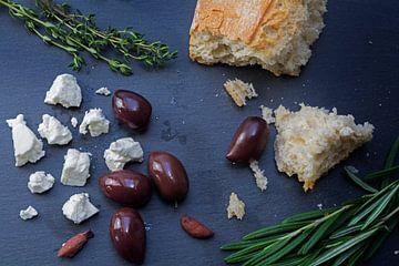 Kalamata-Oliven und Feta-Käse aus Griechenland mit Brot und Kräutern auf dunklem Schiefergrund von Maren Winter