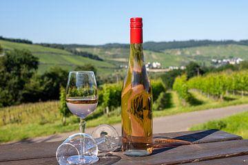 Bouteille de vin et verre à vin rempli sur une table en bois sur Reiner Conrad