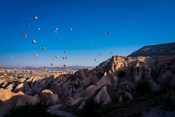 Luchtballonnen boven de bergen in Cappadocia, Turkije van John Ozguc