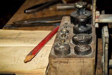 Verstaubter Schreibtisch mit alten Gewichten, Notizen und Schreibgerät von pixxelmixx