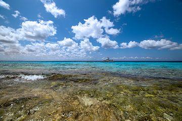 Taucherboot am Horizont, schwimmend auf dem kristallklaren Wasser von Bonaire. von Studio de Waay
