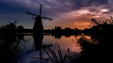 Silhouette van een molen bij Kinderdijk in avondlucht van Michel Seelen