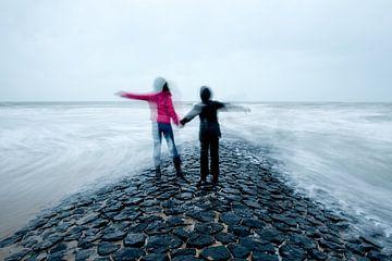 Twee kinderen hand in hand op golfbreker in zee van Remke Spijkers