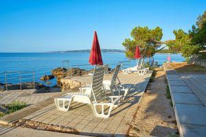 Parasols en ligstoelen op het strand van Krk in Kroatië