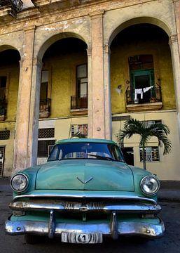Groene oldtimer voor geel gebouw in Havana, Cuba van