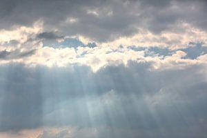 Zonnestralen barsten door de wolken
