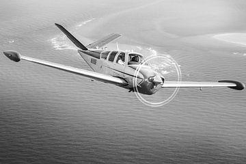 Vintage Beechcraft Bonanza Flugzeug über dem Meer von Planeblogger