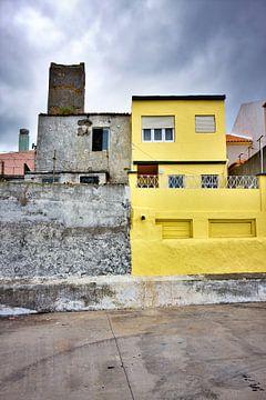 Kleurrijke gele huis donkere wolken