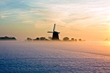 Traditionele hollandse molen in de mist en sneeuw op het platteland van Nederland bij zonsondergang van